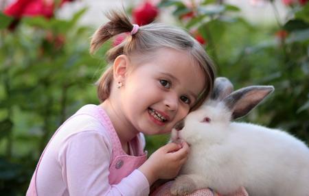 عکس دختر بچه ناز کنار خرگوش سفید پشمالو