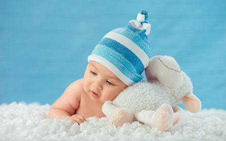 عکس نوزاد تازه متولد شده و عروسک ببعی سفید پشمالو